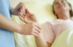врач держит за руки пациентку